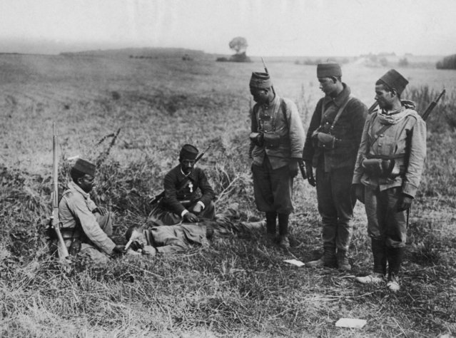 "A group of Tirailleurs or ""Turcos'""(French colonial infantrymen) offer help to a wounded German soldier after the Battle of the Marne, World War I, circa 1914. (Photo by FPG/Hulton Archive/Getty Images)"