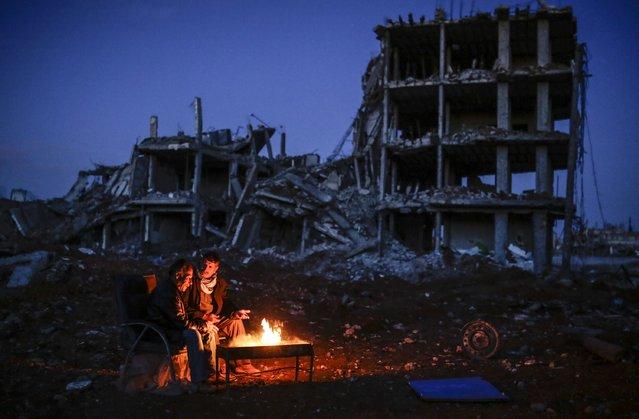 Kurdish men sit near bonfire near a destroyed building, in the Syrian Kurdish town of Kobane, also known as Ain al-Arab, on March 22, 2015. (Photo by Yasin Akgul/AFP Photo)