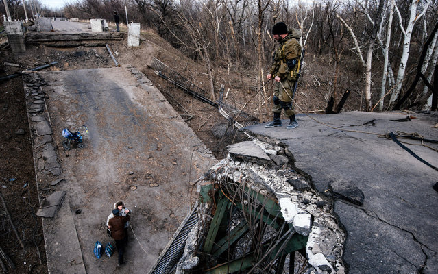 A pro-Russian rebel helps a couple climb on a damaged bridge across the Siversky Donets river near the village of Stanytsia Luhanska on March 23, 2015. (Photo by Dimitar Dilkoff/AFP Photo)