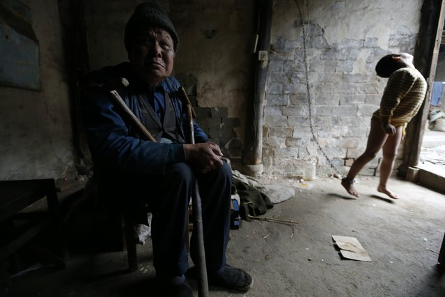 He Zili, 11, is seen chained to a wall as his grandfather sits next to him at their home in Zhejiang province, November 27, 2013. The boy injured his head when he was one-year-old and started suffering from mental disorders. According to his family, they had no choice but to restrain him on chains as he had a tendency to attack those around him. Zili is currently being looked after by his physically disabled grandfather and his intellectually handicapped father after his mother died of cancer. (Photo by William Hong/Reuters)