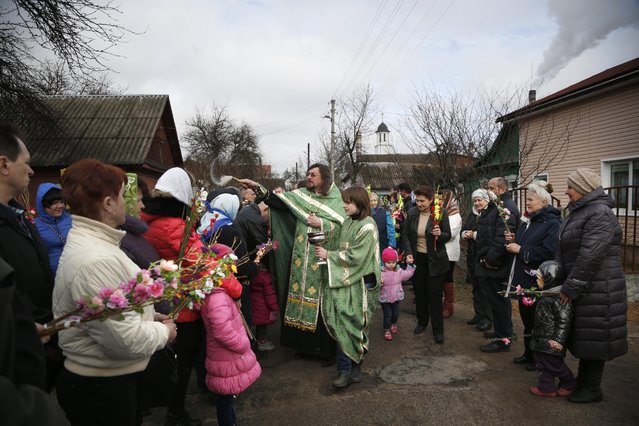 An Orthodox Church priest, center, blesses the faithful holding willow twigs during a mass to mark the Orthodox Christian Palm Sunday in Minsk, Belarus, Sunday, April 5, 2015. In Russia, Ukraine and Belarus, where palms or olive trees don't grow, willow tree twigs are used. (Photo by Sergei Grits/AP Photo)