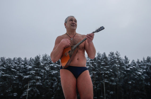 A participant of a festival of winter swimming plays balalaika after taking a dip into the ice water in the town of Podolsk, south of Moscow, Russia January 5, 2017. (Photo by Maxim Shemetov/Reuters)