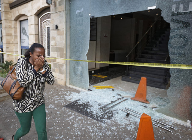 A woman reacts as she flees the scene at a hotel complex in Nairobi, Kenya Tuesday, January 15, 2019. An upscale hotel complex in Kenya's capital came under attack on Tuesday, with a blast and heavy gunfire. The al-Shabab extremist group based in neighboring Somalia claimed responsibility and said its members were still fighting inside. (Photo by Ben Curtis/AP Photo)