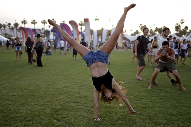 A woman cartwheels through the Coachella Valley Music and Arts Festival in Indio, California April 10, 2015. (Photo by Lucy Nicholson/Reuters)