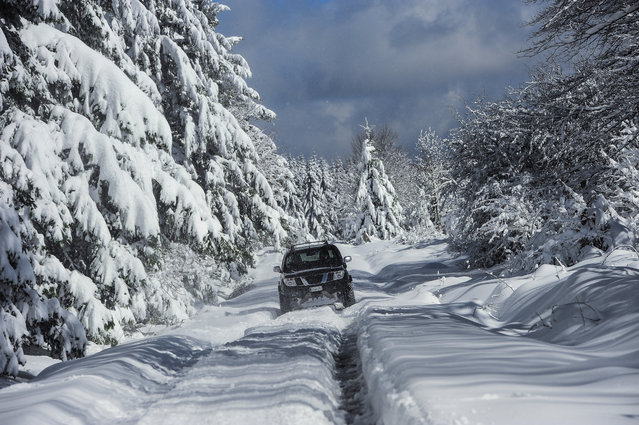 A car moves on a small road covered with snow near to the small village of Opakua, northern Spain, Tuesday, February 16, 2016. After beginning a mild winter the temperatures hves fallen in the north of the country with snow, rain and cold winds. (Photo by Alvaro Barrientos/AP Photo)
