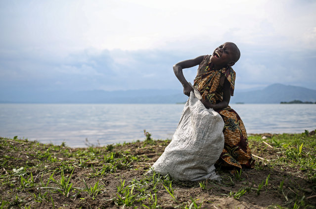 A 10-year-old Pygmy girl laughs as she works weeding the land of a Bahavu farmer on the shore of Lake Kivu on Idjwi island in the Democratic Republic of Congo, November 24, 2016. (Photo by Therese Di Campo/Reuters)