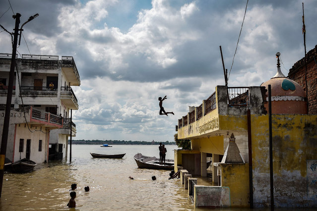 A child playfully jumps into the water accumulated at a flooded area next to a house after rising water levels in the rivers caused flooding at Jhusi area of Allahabad on August 6, 2021. (Photo by Sanjay Kanojia/AFP Photo)