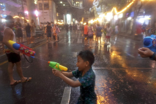 A child uses a water gun as he participates in a water fight during Songkran Festival celebrations at Silom road in Bangkok April 12, 2015. (Photo by Athit Perawongmetha/Reuters)
