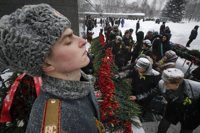 People place flowers to the Motherland monument at the Piskaryovskoye Cemetery where most of the Leningrad Siege victims were buried during World War II, in St. Petersburg, Russia, Saturday, January 26, 2019. People gathered to mark the 75th anniversary of the battle that lifted the Siege of Leningrad. The Nazi German and Finnish siege and blockade of Leningrad, now known as St. Petersburg, was broken on Jan. 18, 1943 but finally lifted Jan. 27, 1944. More than 1 million people died mainly from starvation during the 900-day siege. (Photo by Dmitri Lovetsky/AP Photo)