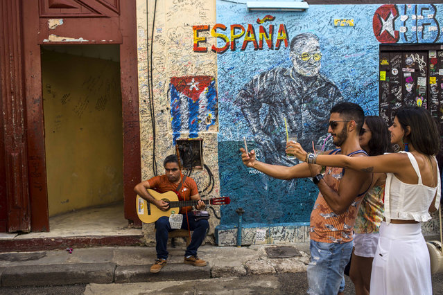 A street musician plays his guitar as tourists take selfies in Havana, Cuba, Wednesday, December 5, 2018. Cuba is softening the impact of a heavily criticized new law that would have given government inspectors power to shut down any exhibition or performance deemed to violate the country's socialist revolutionary values. (Photo by Desmond Boylan/AP Photo)