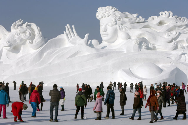 People view a large snow sculpture with the 117-meter-long and 26-meter-high at the 26th Harbin International Snow Sculpture Art Expo in Sun Island park on December 22, 2013 in Harbin, China. The Harbin International Ice and Snow Sculpture Festival is one of the largest ice and snow festivals in the world and is a popular winter destination for both Chinese and foreign visitors. (Photo by Hong Wu/Getty Images)