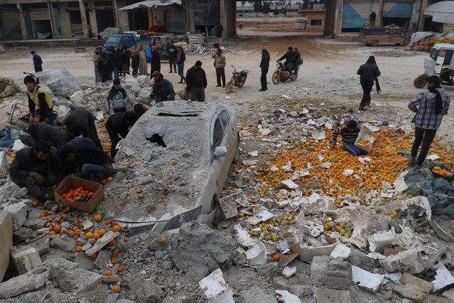 People collect scattered oranges amidst rubble after an airstrike on a market in rebel held Maarrat Misrin city in Idlib province, Syria January 14, 2017. (Photo by Ammar Abdullah/Reuters)