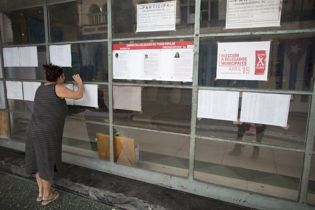 A woman looks through the window of a polling station to be used for the municipal elections in Havana, April 18, 2015. (Photo by Alexandre Meneghini/Reuters)