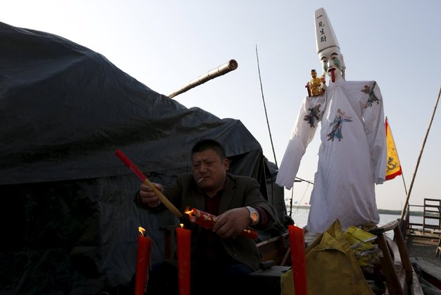 A man burns incense as he prays to the God of Fortune during a boat festival in Wangjiangjing township, Zhejiang province, April 15, 2015. (Photo by William Hong/Reuters)