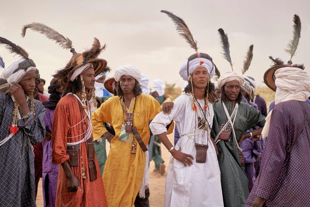 A group of Wodaabe men rest after dancing during the Cure Salee, in Ingall, northern Niger, on September 18, 2021. For three days the Saharan desert of Ingall, in the north of Niger, was draped with the colors of the tunics of thousands of herders who came to celebrate their traditions. (Photo by Michele Cattani/AFP Photo)