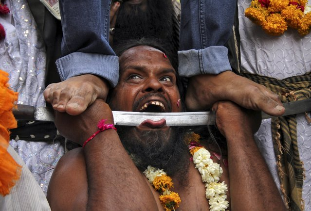 An Indian Muslim devotee, who is on a pilgrimage to the shrine of Sufi saint Khwaja Moinuddin Chishti for Urs, performs a stunt during a procession at Ajmer in the desert Indian state of Rajasthan April 19, 2015. Urs is an annual festival which is held for over six days at Ajmer, commemorating the death anniversary of Sufi saint Chishti. (Photo by Himanshu Sharma/Reuters)