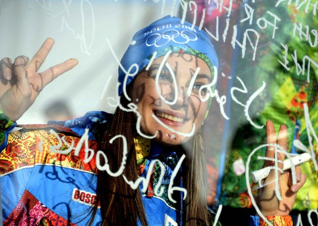 Russian pole vault star Yelena Isinbayeva signs the Olympic Wall of Truce during a visit at the Olympic Village on February 4, 2014 in Sochi before the start of the 2014 Sochi Winter Olympic Games. (Photo by Alexander Nemenov/AFP Photo)