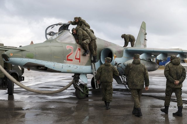 Support personnel prepare a Russian Sukhoi Su-25 fighter jet before the take-off, part of the withdrawal of Russian troops from Syria, at Hmeymim airbase, Syria, March 16, 2016. (Photo by Vadim Grishankin/Reuters/Russian Ministry of Defence)