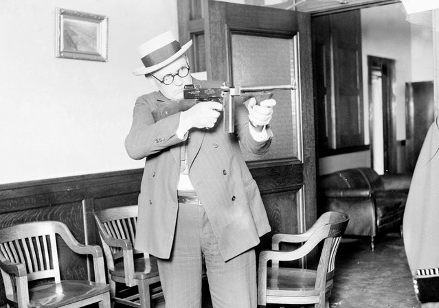 Lieutenant William Shoemacher stands and aims a Thompson machine gun, or tommy gun, Chicago, 1926. The gun, developed for World War I, was very popular with gangsters due to its high rate of fire. From the Chicago Daily News collection. (Photo by Chicago History Museum/Getty Images)
