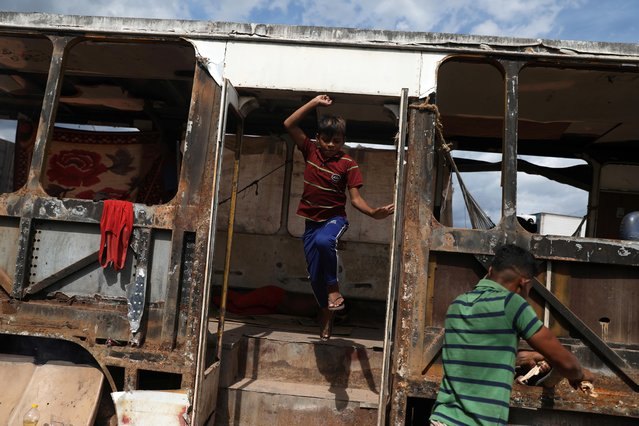 Venezuelan Erasmo Valderrama jumps out of the bus where he lives with his father and other people in the border city of Pacaraima, Brazil on April 13, 2019. Two children go to the local school every morning. The penniless migrants work at odd jobs for spare change, loading the cars and pickups of Venezuelans who cross over to buy food and goods in short supply back home. (Photo by Pilar Olivares/Reuters)