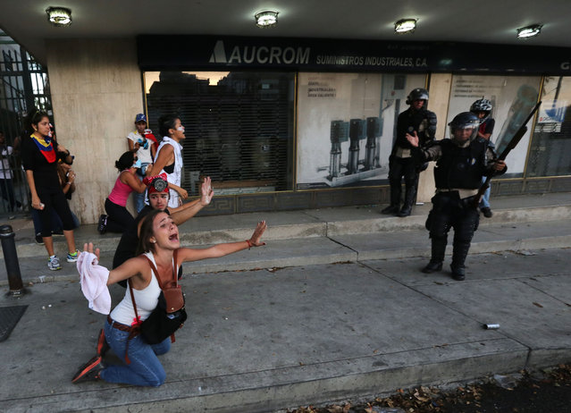 An opposition demonstrator shouts for the National Bolivarian Police (BNP) to not fire tear gas at them as a member of the force, right, gestures after his superior ordered them to hold their fire, during clashes in Caracas, Venezuela, Saturday, February 15, 2014. Venezuelan security forces backed by water tanks and tear gas are dispersing groups of anti-government demonstrators who tried to block Caracas' main highway Saturday evening. (Photo by Fernando Llano/AP Photo)