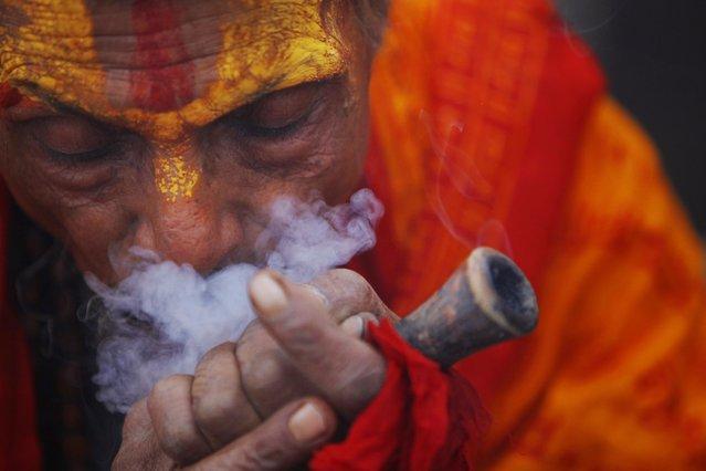 A Hindu holy man smokes marijuana in the courtyard of the Pashupatinath Temple in Katmandu, Nepal, Wednesday, February 26, 2014. (Photo by Niranjan Shrestha/AP Photo)