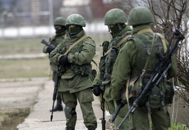 Unidentified gunmen guard Ukraine's infantry base in Privolnoye, Ukraine, Sunday, March 2, 2014. (Photo by Darko Vojinovic/AP Photo)