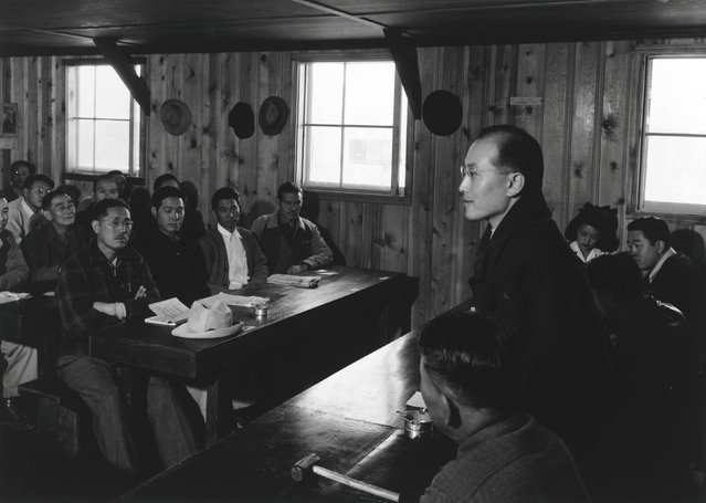 Roy Takeno, standing, addresses a group of men gathered for a town hall meeting at the Manzanar War Relocation Center in California, in this 1943 handout photo. (Photo by Courtesy Ansel Adams/Library of Congress, Prints and Photographs Division/Reuters)