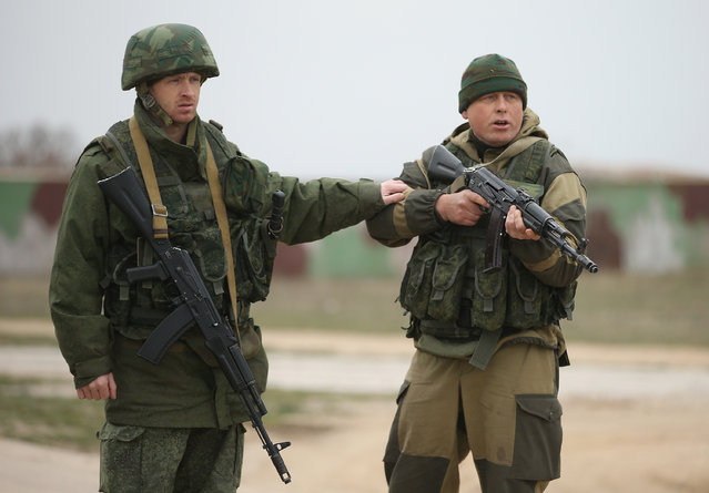 A soldier under Russian command restrains a colleague after he fired his weapon into the air and screamed orders to turn back at an approaching group of over 100 unarmed Ukrainian troops at the Belbek airbase, which the Russian troops are occcupying, in Crimea on March 4, 2014 in Lubimovka, Ukraine. (Photo by Sean Gallup/Getty Images)