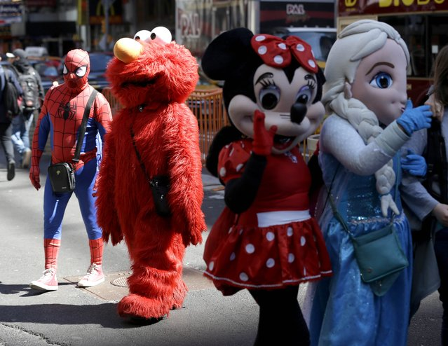 Costumed characters work for tips in Times Square in New York, Tuesday, March 29, 2016. The costumed characters, naked painted ladies and bus tour ticket sellers who have made all of Times Square their stomping grounds could be restricted to specific zones under legislation being considered by the City Council. The council's committee on transportation is holding a hearing Wednesday morning on legislation that would allow the city's Department of Transportation to create rules and regulations for pedestrian plazas like the ones in Times Square. (Photo by Seth Wenig/AP Photo)