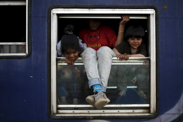 Children look out from a train wagon at a makeshift camp for migrants and refugees at the Greek-Macedonian border near the village of Idomeni, Greece, March 30, 2016. (Photo by Marko Djurica/Reuters)