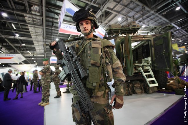A French soldier stands near a military combat command vehicle on display at The Defence and Security Exhibition