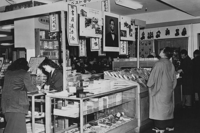 Interior of a Tokyo department store in 1959, where a Japanese man wearing Geta, traditional wooden footwear, looks up at a poster-sized portrait of Abraham Lincoln hanging with two other posters about Lincoln's life. (Photo by Library of Congress via The Atlantic)