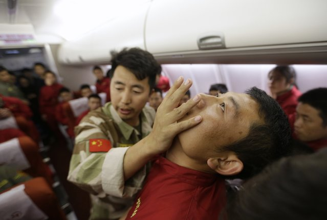 An instructor from the Tianjiao Special Guard/Security Consultant bodyguard training camp pushes a student's jaw as trainees watch him demonstrate close-quarter combat skills during a special course on flight safety inside a scale model of a passenger jet at a flight attendant training centre on the outskirts of Beijing, March 18, 2014. (Photo by Jason Lee/Reuters)