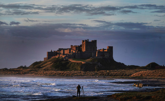 A photographer lines up his shot at Bamburgh Castle in Northumberland, England on May 7, 2019. (Photo by Owen Humphreys/PA Wire Press Association)