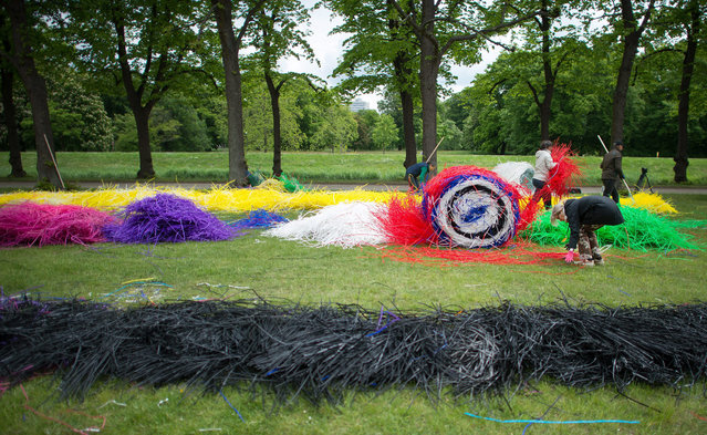 Assistants sort multi-colored drinking straws for the art action by sculptor and installation artist Michael Beutler in the Herrenhausen Gardens in Hanover, Germany, 21 May 2015. Artworks by Beutler and others can be seen during the annual art festival taken place from 29 May to 14 June. (Photo by Jochen Luebke/EPA)