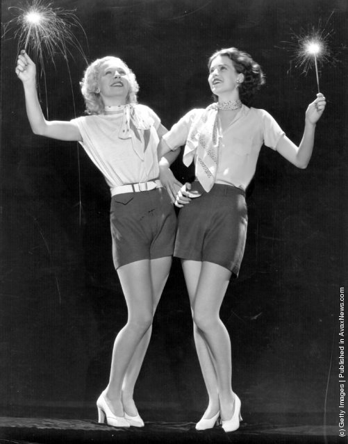 1932: Elizabeth Young, a Paramount player of the 30's is celebrating Independence Day by waving sparklers and linking arms with Lyda Roberti the German-Polish leading lady who was a former child cafe singer