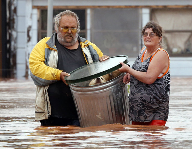 George and Susan Kruger make one of three trips with their animals from their flooded house to safety on Sunday, May 24, 2015 in Purcell, Okla. Rising water from overnight rains began to rise early in the morning.  The Krugers refused to leave their home and made several trips to retrieve five dogs and a baby chick. (Photo by Steve Sisney/The Oklahoman via AP Photo)
