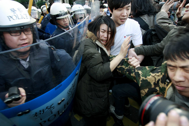 Students protesting against a China Taiwan trade pact are forced by riot police to leave the government Cabinet buildings in Taipei, Taiwan, Monday, March 24, 2014. Hundreds of protesters opposed to a far-reaching trade pact with China invaded Taiwan's Cabinet offices, marking a sharp escalation in a student-led movement against the island's rapidly developing ties with the communist mainland. (Photo by Wally Santana/AP Photo)