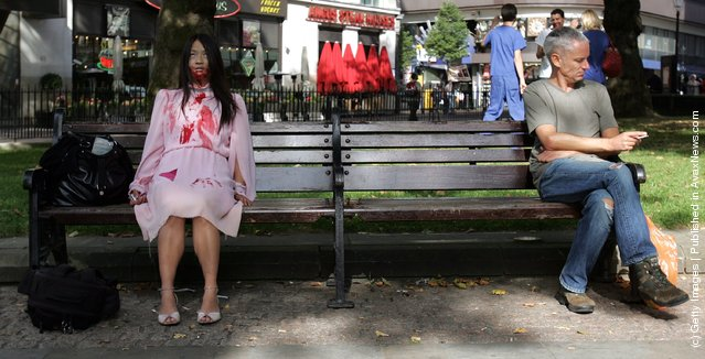 A woman dressed as a Zombie sits in Leicester Square during the zombie walk
