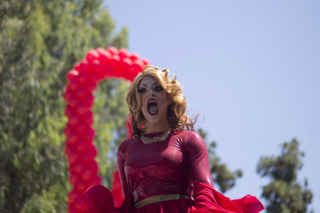 A drag queen sings during the annual Gay Pride Parade on a street of Tel Aviv, Tel Aviv, Israel, Friday, June 12, 2015. Thousands of bare-chested muscular men, drag queens in heavy makeup and high heels, women in colorful balloon costumes and others partied at Tel Aviv's annual gay pride parade on Friday, the largest event of its kind in the region. (AP Photo/Ariel Schalit)