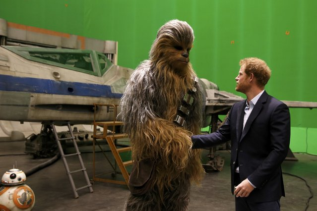 Britain's Prince Harry meets Chewbacca during a visit to the Star Wars film set at Pinewood Studios near Iver Heath, west of London, Britain, April 19, 2016. Prince William and Prince Harry are touring Pinewood to visit the production workshops and meet the creative teams working behind the scenes on the Star Wars films. (Photo by Adrian Dennis/Reuters)