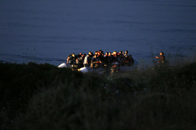 A dinghy overcrowded with Syrian migrants arrives from Turkish coasts at a beach in Mytilene, on the northeastern Greek island of Lesvos, early Tuesday, June 16, 2015. Lesvos has been bearing the brunt of a huge influx of migrants from the Middle East, Asia and Africa crossing from the Turkish coast to nearby Greek islands. More than 50,000 migrants have arrived in Greece already this year, compared to 6,500 in the first five months of last year. (AP Photo/Thanassis Stavrakis)
