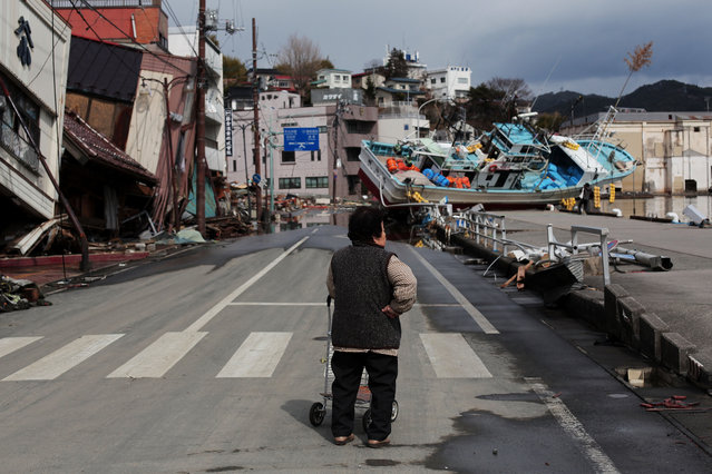 A woman surveys the damage after the earthquake on March 17, 2011 in Kensennuma, Japan. Residents were allowed back to their homes today and began the massive cleanup operation caused by a 9.0 magnitude strong earthquake that struck on March 11 off the coast of north-eastern Japan. The quake triggered a tsunami wave of up to 10 metres which engulfed large parts of north-eastern Japan. The death toll has risen past 5000 with at least 8600 people still missing. (Photo by Chris McGrath/Getty Images)