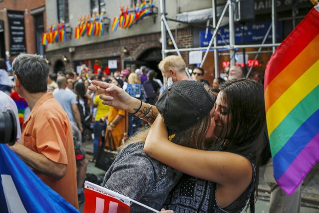 Women kiss each other as people celebrate outside the Stonewall Inn in the Greenwich Village neighborhood of New York June 26, 2015. The Supreme Court ruled on Friday that the U.S. Constitution provides same-s*x couples the right to marry, handing a historic triumph to the American gay rights movement. (Photo by Eduardo Munoz/Reuters)