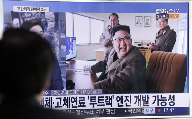 """A man watches a TV news program showing an image, published in North Korea's Rodong Sinmun newspaper, of North Korean leader Kim Jong Un at the country's Sohae launch site, at Seoul Railway station in Seoul, South Korea, Sunday, March 19, 2017. North Korea has conducted a ground test of a new type of high-thrust rocket engine that leader Kim Jong Un is calling a revolutionary breakthrough for the country's space program. The letters read """"New type engine"""". (Photo by Ahn Young-joon/AP Photo)"""
