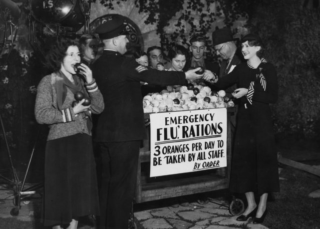 """Actress Molly Lamont receiving her orange """"rations"""" from a sergeant at Elstree Studios, London, circa 1940. It is being advised that everyone eat three oranges a day following a """"flu epidemic"""", which has claimed over 200 victims at the studios. (Photo by Fox Photos/Getty Images)"""