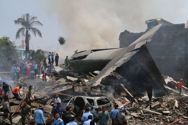 Officials and rescue personnel work at the scene where an Indonesian military C-130 Hercules crashed into a residential area in Medan on June 30, 2015. An Indonesian military transport plane crashed on June 30 shortly after take-off in a city on Sumatra island, exploding in a ball of flames in a residential area. (Photo by Kharisma Tarigan/AFP Photo)