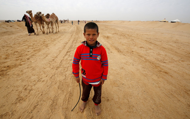 Fahad, an 8-year-old jockey, looks on during the opening of the International Camel Racing festival at the Sarabium desert in Ismailia, Egypt, March 21, 2017. (Photo by Amr Abdallah Dalsh/Reuters)