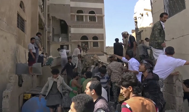In this frame grab from from video, people search in the rubble following Saudi-led coalition airstrikes that killed at least six, including children, officials said, in the residential center of the capital, Sanaa, Yemen. The Sanaa airstrikes came after Yemen's Iran-backed Houthi rebels, who control the capital, launched a drone attack earlier in the week on a critical oil pipeline in Saudi Arabia, Tehran's biggest rival in the region. (Photo by AP Photo)